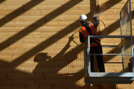 preservative: Tradesman spray painting the wall of a wooden industrial building with timber preservative Stock Photo