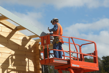 rafter: A builder attaches wire netting to a building in preparation for putting on the roof Editorial