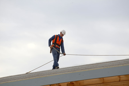 A builder secures safety lines for men about to put the roof on a large commercial building Stockfoto