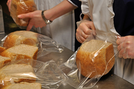 caterers bag up small loaves of bread for guests at a reception