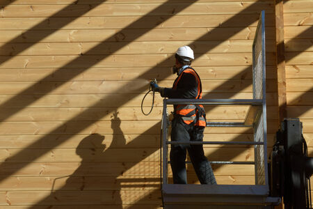 labouring: Tradesman spray painting the wall of a wooden industrial building with timber preservative Stock Photo