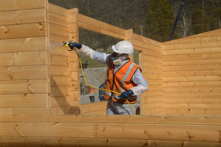 tradesman: Tradesman spray painting the wall of a wooden industrial building with timber preservative Stock Photo