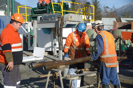 hydrocarbon: Drilling crewmen prepare to remove a core sample from a rig drilling near Greymouth, New Zealand. Stock Photo