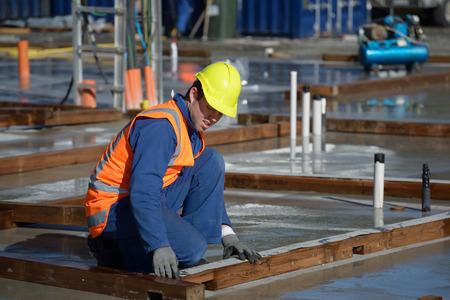 damp: Un costruttore pone naturalmente umido sulle tavole di base per un grande edificio Archivio Fotografico