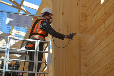 Tradesman spray painting the wall of a wooden industrial building with timber preservative Standard-Bild