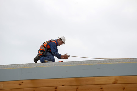 A builder secures safety lines for men about to put the roof on a large commercial building Stok Fotoğraf