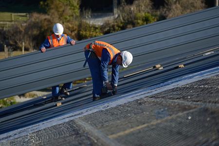 Een bouwer schroeven naar beneden dakbedekking ijzer voor het dak op een groot commercieel gebouw in de buurt van Greymouth, Nieuw-Zeeland Stockfoto