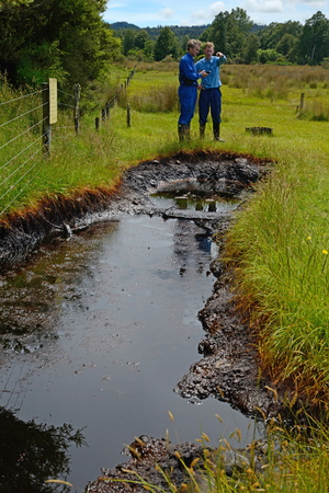 seep: A couple of oil prospectors take GPS readings at a natural oil seep at Kotuku near Greymouth, West Coast, New Zealand. This seep has inspired oil exploration in the area since the early 1900s.