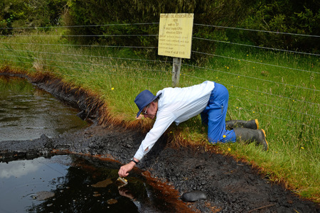 seep: An oil prospector samples crude oil from a natural oil seep at Kotuku near Greymouth, West Coast, New Zealand. This seep has inspired oil exploration in the area since the early 1900s. Stock Photo