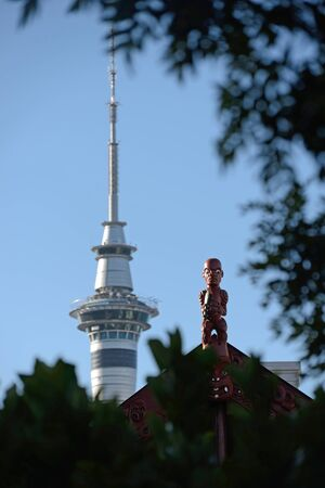 opposites: A carving of a Maori warrior stands guard over a marae while the modern Sky Tower dominates the Auckland skyline in New Zealand