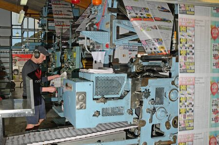 workmanship: GREYMOUTH, NEW ZEALAND, MAY 22, 2015:  An unidentified printer checks the quality of his workmanship while printing a newspaper on May 22, 2015 in Greymouth, New Zealand.