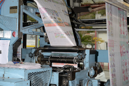 labouring: GREYMOUTH, NEW ZEALAND, MAY 22, 2015:  Newsprint speeds through the folder while printing a newspaper on May 22, 2015 in Greymouth, New Zealand.