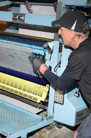 labouring: GREYMOUTH, NEW ZEALAND, MAY 22, 2015:  An unidentified printer removes the plates after printing a newspaper on May 22, 2015 in Greymouth, New Zealand. Editorial