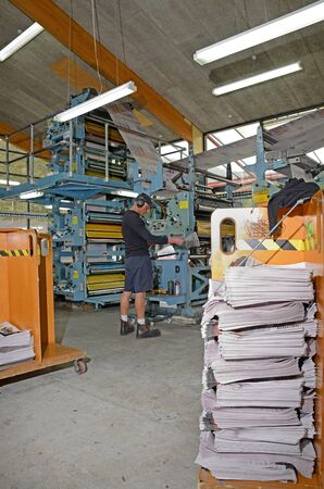 labouring: GREYMOUTH, NEW ZEALAND, MAY 22, 2015:  An unidentified printer checks the quality of his workmanship while printing a newspaper on May 22, 2015 in Greymouth, New Zealand.