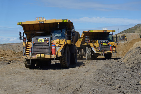 WESTPORT, NEW ZEALAND, MARCH 11, 2015: 130 ton loads of rock overburden are carried away at the Stockton open cast coal mine on March 11, 2015 near Westport, New Zealand