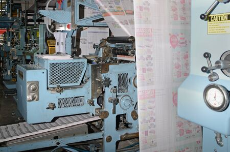 labouring: GREYMOUTH, NEW ZEALAND, MAY 22, 2015:  Advertisements dominate the pages  while printing a newspaper on May 22, 2015 in Greymouth, New Zealand.