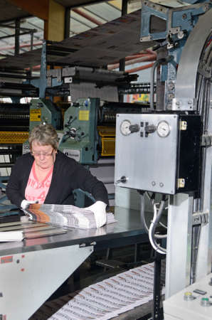 labouring: GREYMOUTH, NEW ZEALAND, MAY 22, 2015:  An unidentified woman bundles up newspapers as they are printed on May 22, 2015 in Greymouth, New Zealand. Editorial