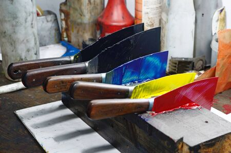 labouring: Broadknives laded with ink wait to be used while printing a newspaper