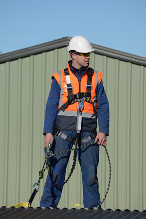 descender: A builder wearing a safety harness while working at heights waits for instructions from the foreman Stock Photo