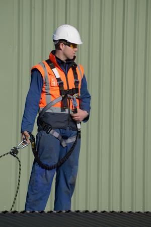 높이에서 일하는 동안 안전 장치를 착용 한 건축업자는 감독 인의 지시를 기다린다.