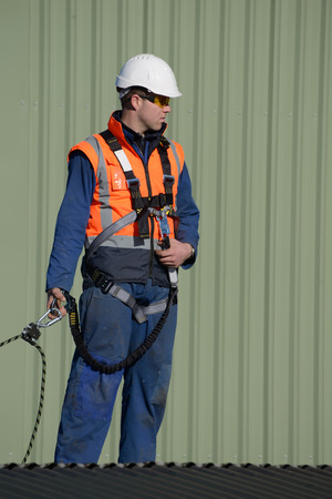 A builder wearing a safety harness while working at heights waits for instructions from the foreman Stock Photo