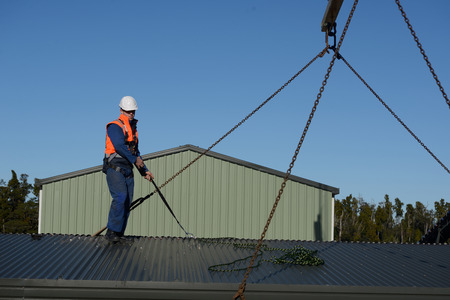 A builder wearing a safety harness helps to place the sling in place for a crane to lift a portable building