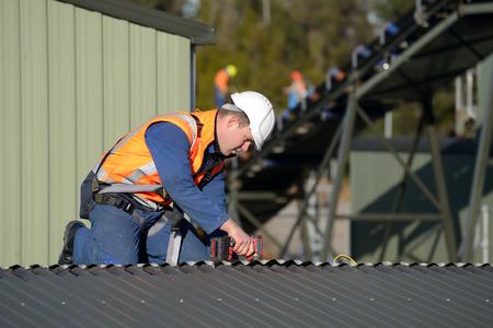 Een bouwer die een veiligheidsharnas voor het werken op hoogte schroeft dakbedekking ijzer op een gebouw gemarkeerd voor de sloop