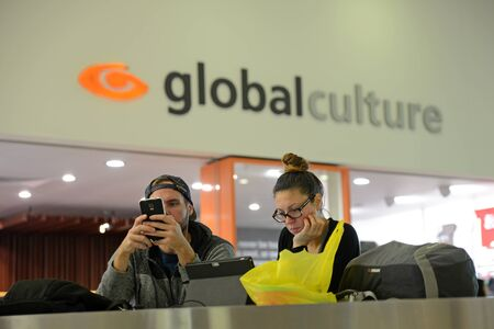 absorbed: CHRISTCHURCH, NEW ZEALAND, JULY 12, 2015: An unidentified couple absorbed in their digital world outside the Global Culture cafe at Christchurch Domestic Airport, New Zealand, July 12, 2015
