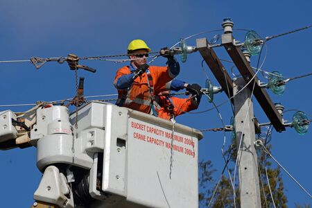 linesman: GREYMOUTH, NEW ZEALAND, AUGUST 5, 2015: A linesman wires up a mains power supply cable on a new pole near Greymouth, August 5, 2015