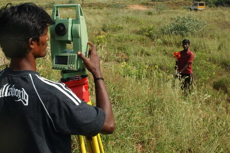 land surveying: TAMIL NADU, INDIA, circa 2009: Men surveying land in Tamil Nadu, India