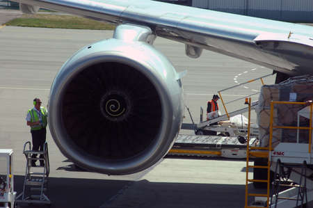 carry out: CHRISTCHURCH, CIRCA 2010: Technicians carry out routine maintenance on a commercial jet  between flights at Christchurch International Airport.