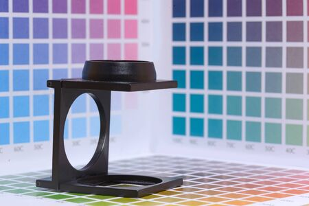 prepress: a magnifier or printers loupe sits on a colour test sheet in a pre-press workshop