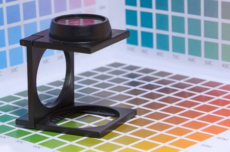 a magnifier or printers loupe sits on a colour test sheet in a pre-press workshop