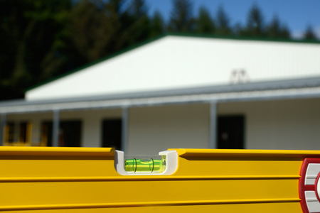 leveling: detail of the bubble in a spirit level with a new building in the background