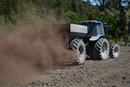 spreads: A tractor spreads blood and bone fertiliser on a paddock in Westland, New Zealand Stock Photo