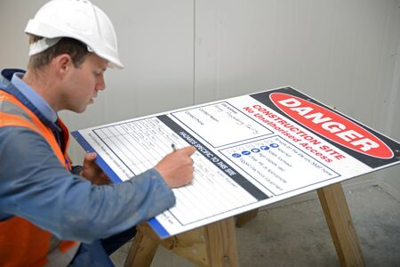 posted: A builder fills out the hazards board to be posted outside the construction site Stock Photo