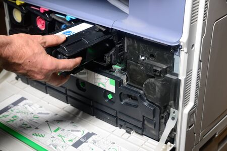 replaces: An office worker replaces a black toner cartridge in a photocopier