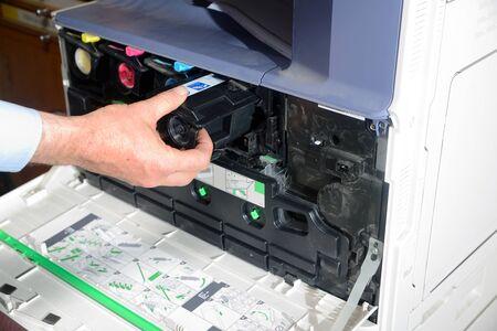 fotocopiadora: Un empleado de oficina reemplaza un cartucho de t�ner negro en una fotocopiadora