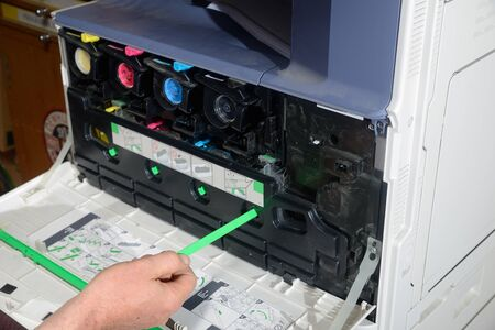 fotocopiadora: Un empleado de oficina limpia el mecanismo en una fotocopiadora