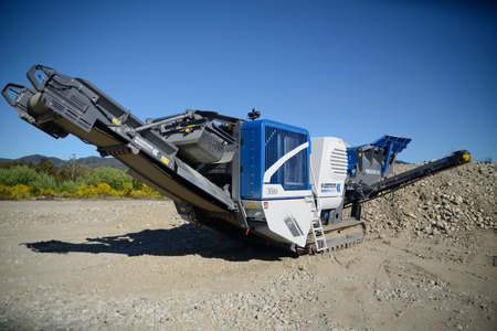mc: WEST COAST, NEW ZEALAND, November 5, 2015: A new Kleeman Mobicat MC 110Z rock crusher stands ready for work at a mining operation on the West Coast of New Zealand, 11-5-2015.