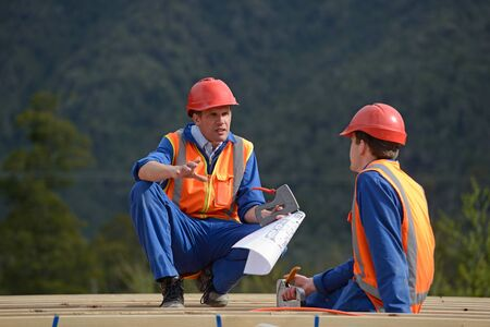 discuss: Two electricians discuss the plan for a major construction job