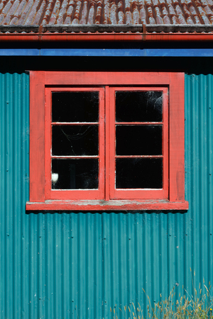 unkempt: Background shot of a window in a colourful old farm building Stock Photo