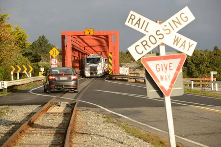 bridging: GREYMOUTH, NEW ZEALAND, APRIL 26, 2016: Traffic waits for oncoming vehicles to cross a single lane road-rail bridge over the Taramakau River near Greymouth Editorial