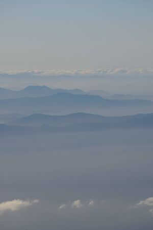 poking: pastel background of mountain tops poking through the mist and cloud