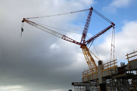 A large crane overshadows a city construction site