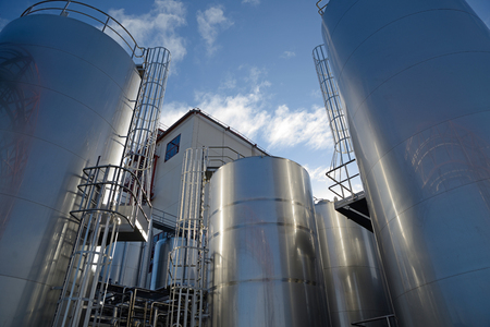 Stainless steel silos store milk products at a factory that manufactures hundreds of products