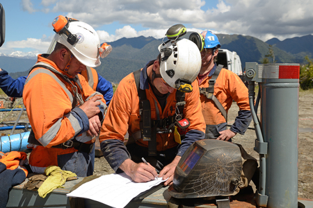 MOANA, NEW ZEALAND, OCTOBER 27, 2017: The safety officer finalises a safety meeting at an abandoned oil well before permitting workers into a  confined space.