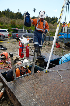 MOANA, NEW ZEALAND, OCTOBER 27, 2017: The safety officer supervises entry into the cellar of an abandoned oil well. Editorial