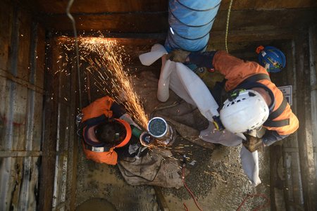 MOANA, NEW ZEALAND, OCTOBER 27, 2017: Sparks fly as engineers work in a confined space to remove the old pipework on an abandoned oil well. Editorial