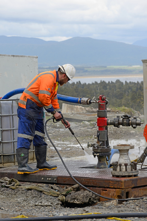 MOANA, NEW ZEALAND, OCTOBER 27, 2017: An unidentified engineer cleans up around an abandoned oil well in preparation for capping the well.